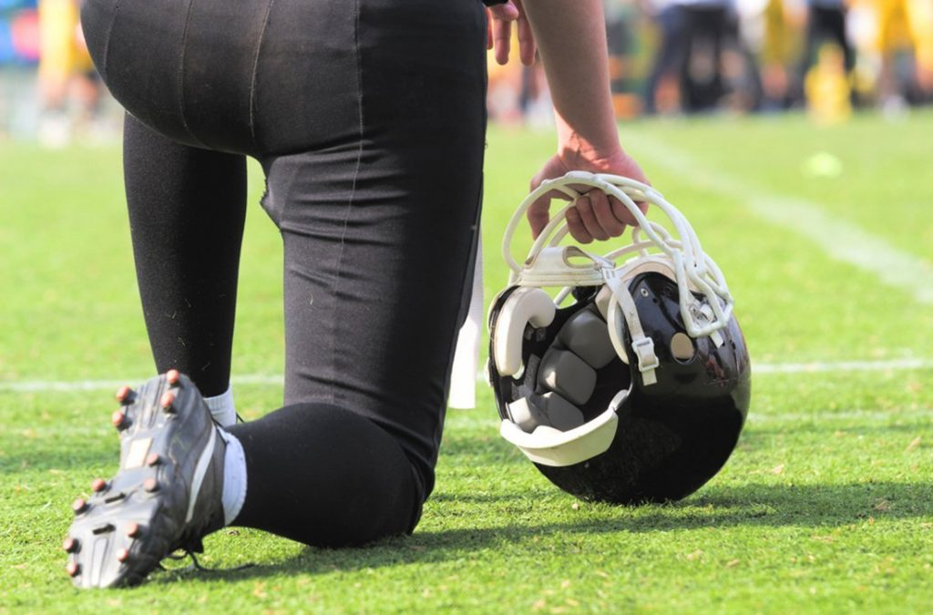 American football player kneeling before game starts