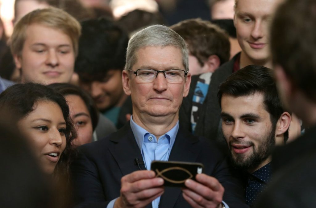 Apple CEO Tim Cook with a mobile phone and people around him