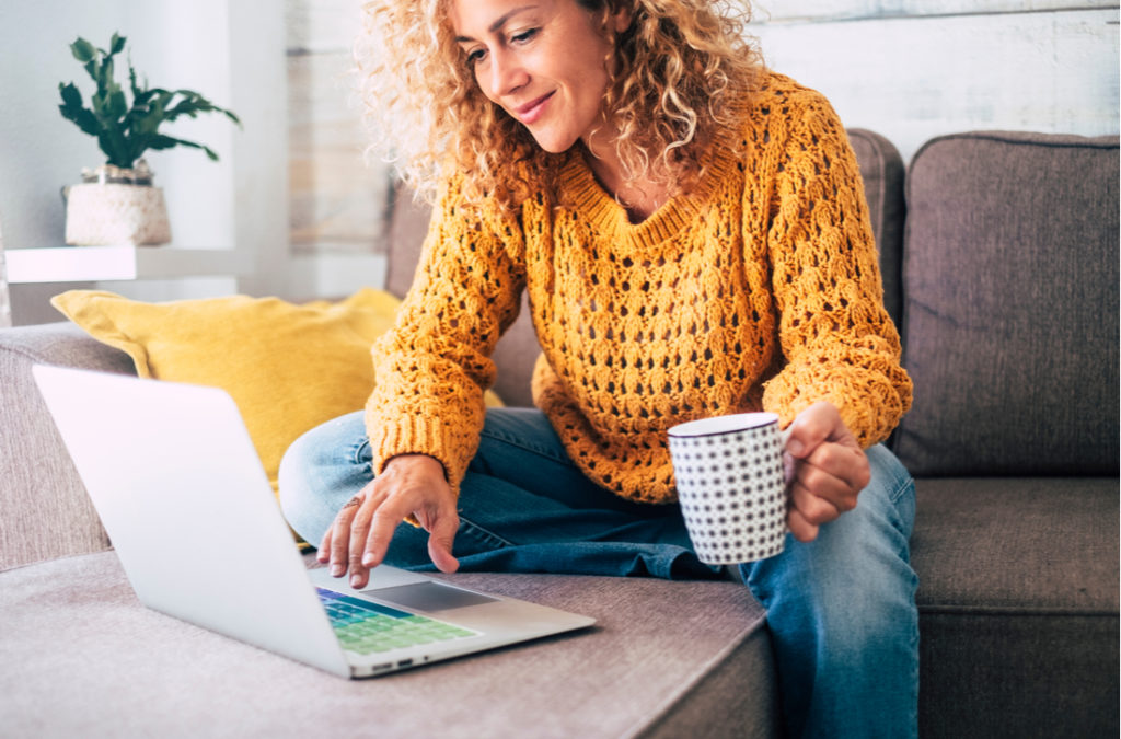 Woman using computer while drinking from a mug